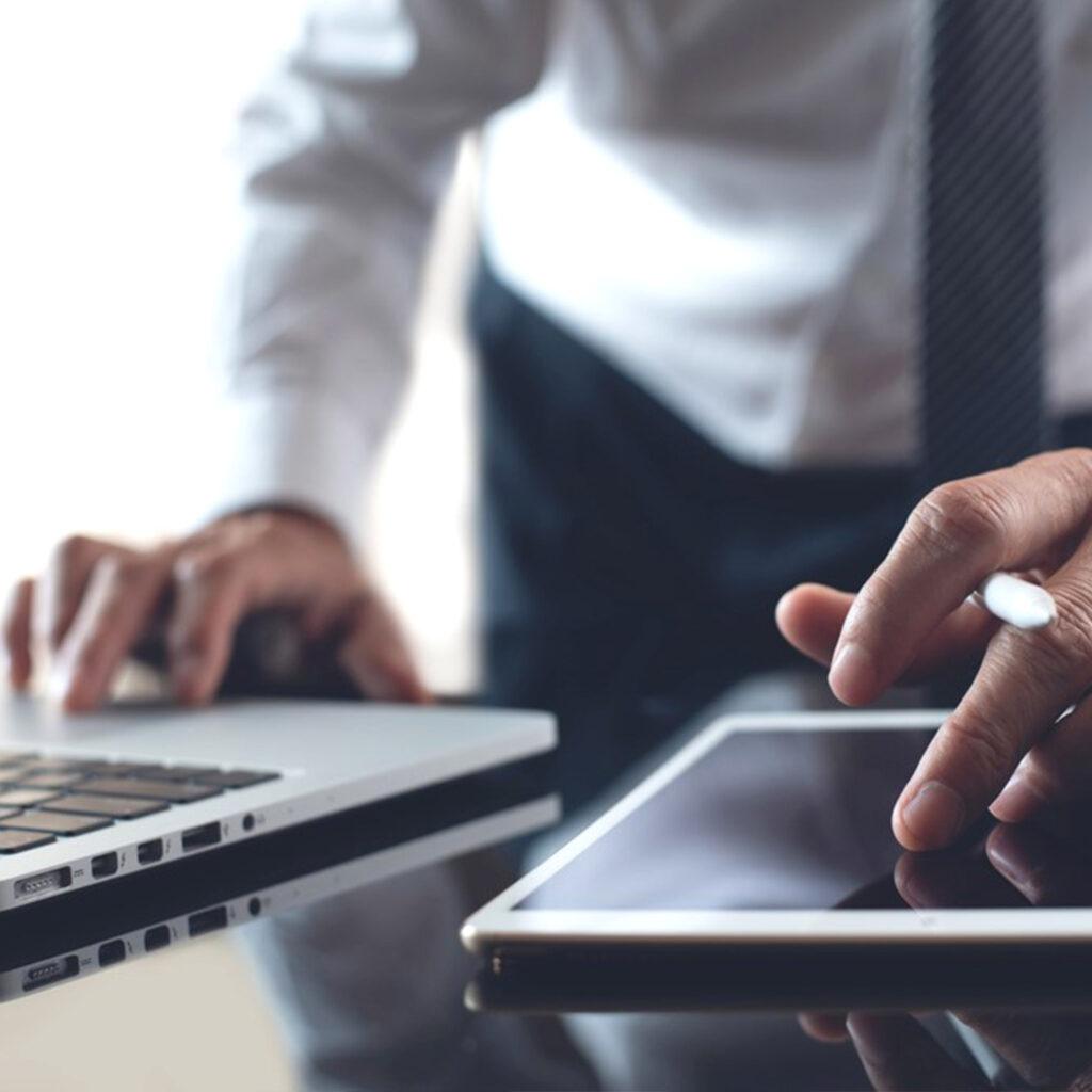 uomo con tablet e portatile