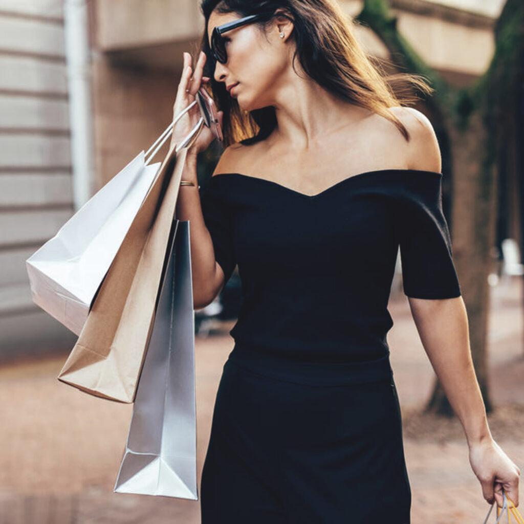 donna con vestito nero e buste shopping