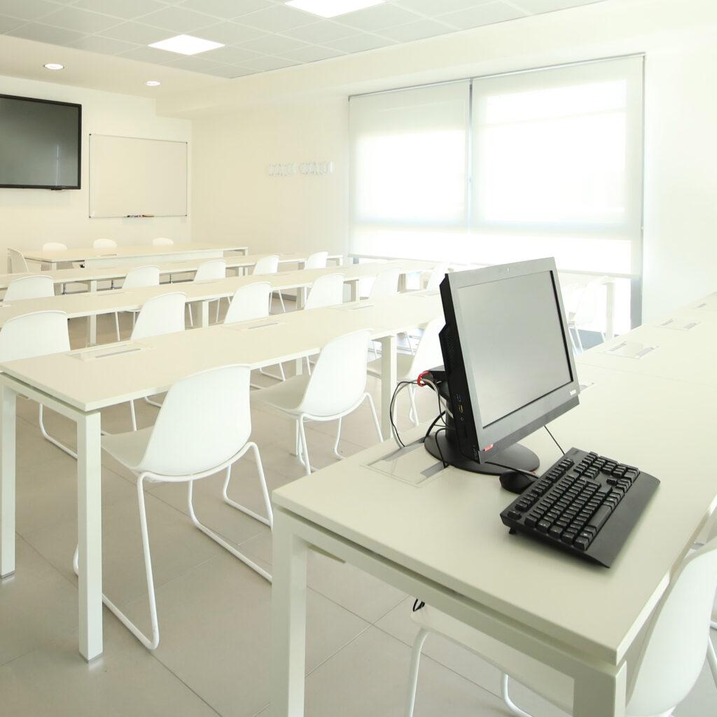 aula vuota con computer in primo piano