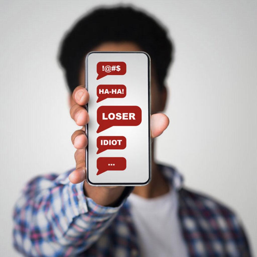 """ragazzo con cellulare in mano e schermata con parole """"cyberbullismo"""""""